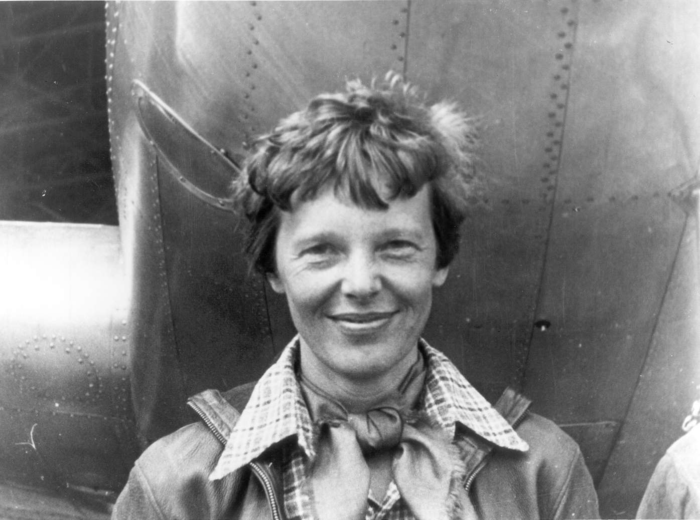 Amelia Earhart close up standing in front of a plane.