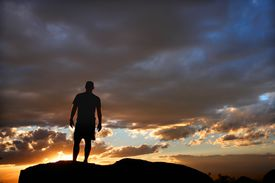 silhouette of a man against a cloudy sunset