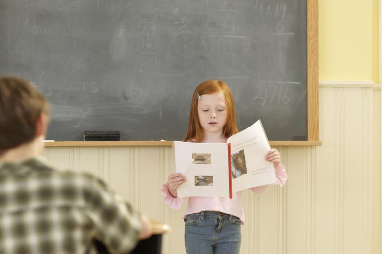 Girl (6-8) standing at blackboard, giving presentation in class