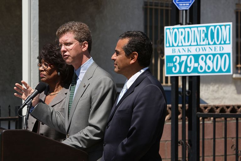 HUD Secretary Donovan standing in front of foreclosed home
