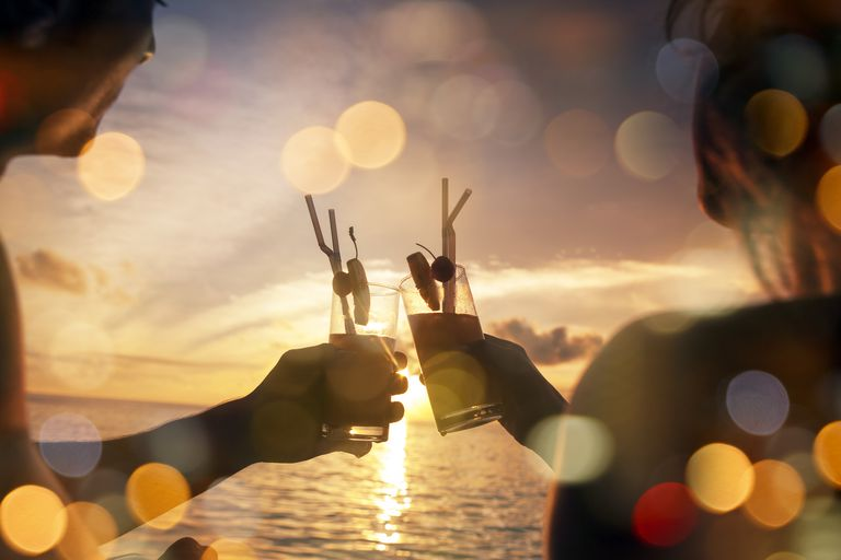Couple on a beach at sunset clinking glasses together.