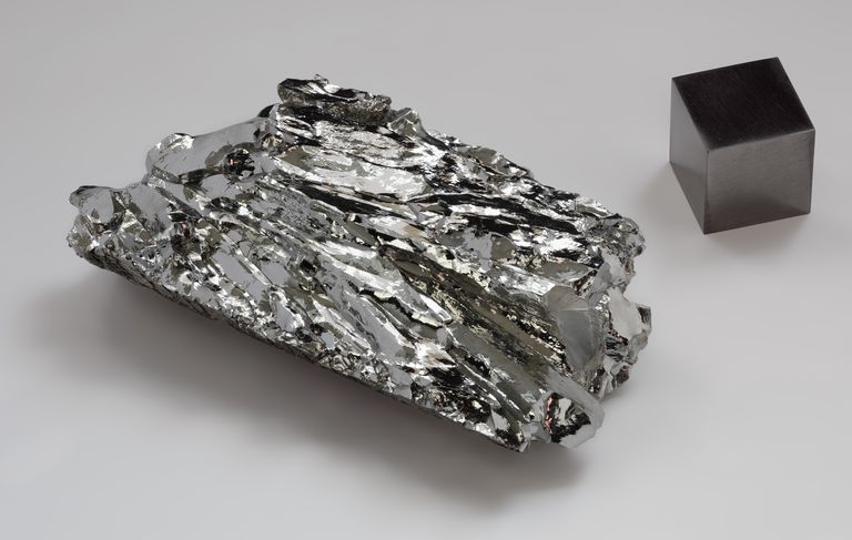 A piece of crystalline molybdenum and a cube of molybdenum metal
