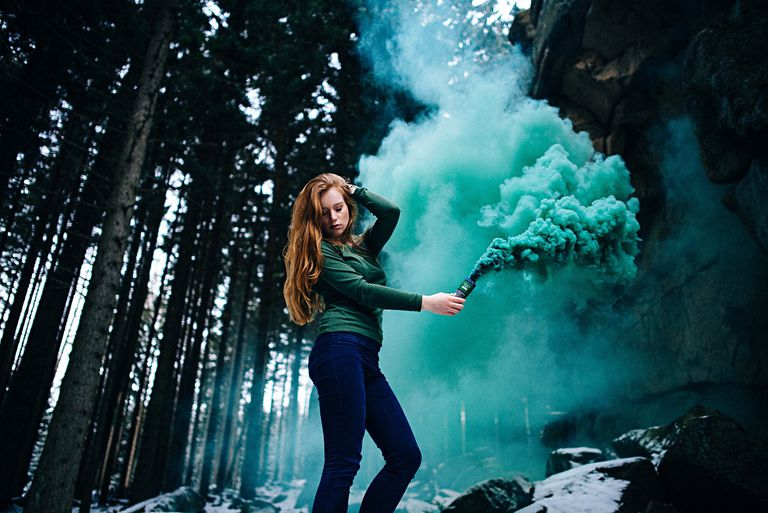 A young woman in a forest holding a distress flare