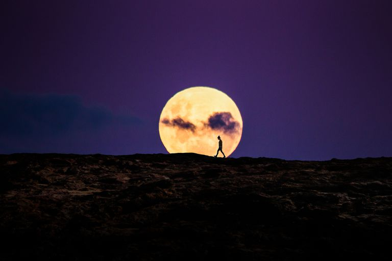 Silhouette of person walking in front of a rising super moon on the rocky coast of Australia