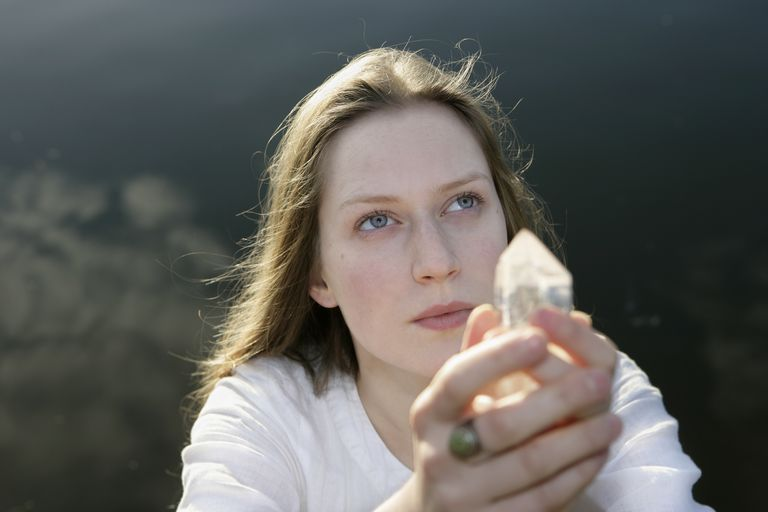Young woman by lake holding crystal, looking up