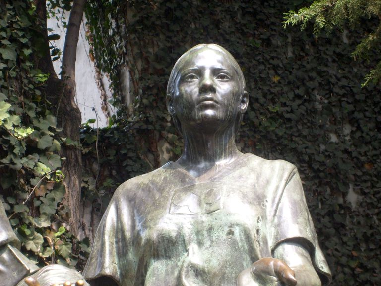 Close up of a statue of la Malinche in a wooded area with vines growing.