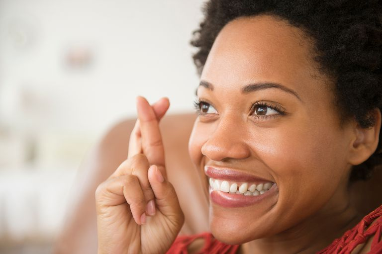 Close up of woman smiling with fingers crossed.