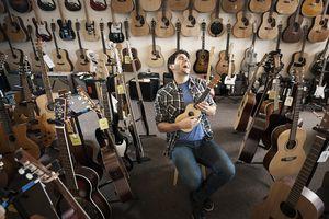 Man Testing Guitar in Shop