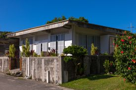 one story flat roofed concrete home with shutters behind a short wall near a flowering bush
