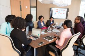 Women in a conference room viewing a presentation on a big screen.