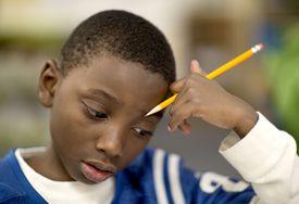 Fourth grade boy works on a math problem.