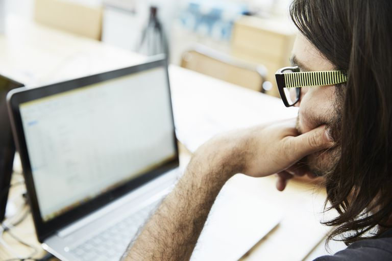 Over shoulder close up of male office worker looking at laptop in office