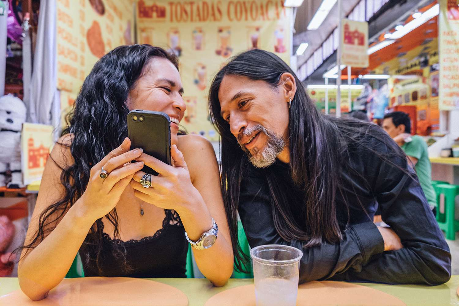 Woman and man looking at mobile phone in Mexican market