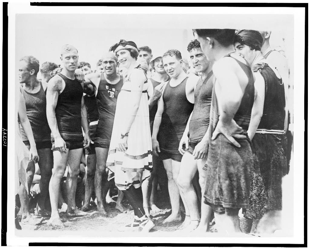 Group of people, in swimsuits, standing on beach
