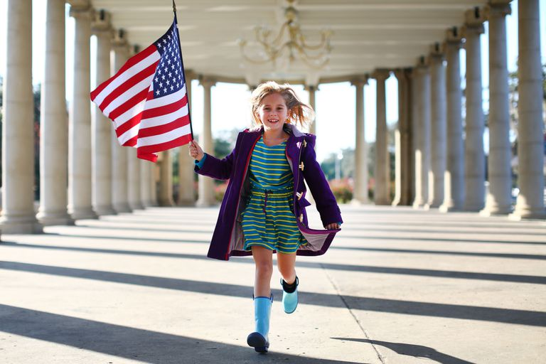 Niña corriendo con una bandera americana en sus manos.