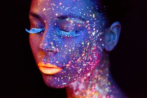 This woman is wearing make-up that glows under a black light.