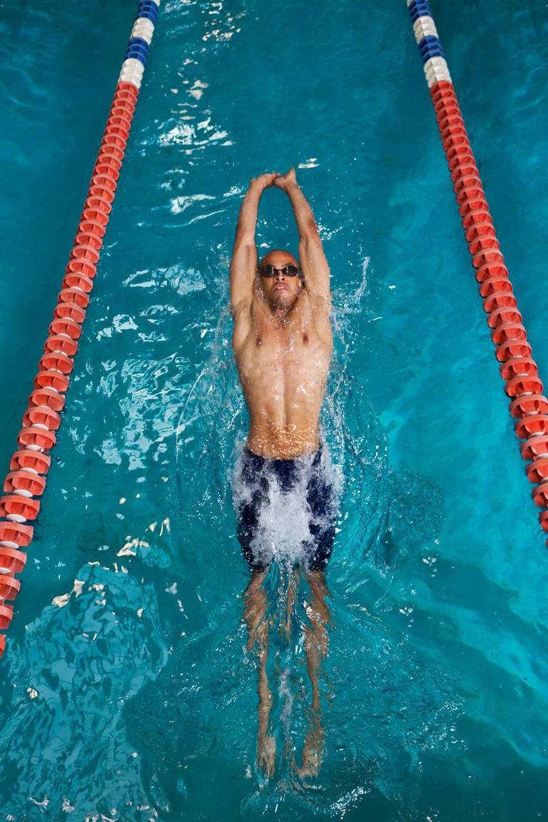 Male swimmer pushing off wall in pool