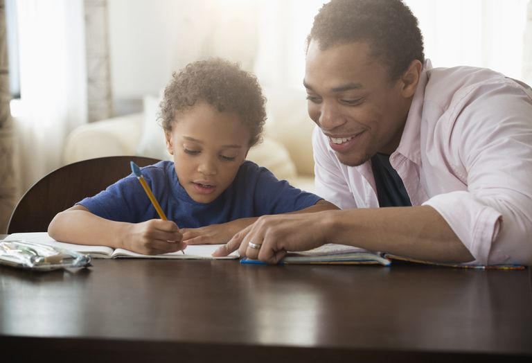 Mixed race father helping son with homework