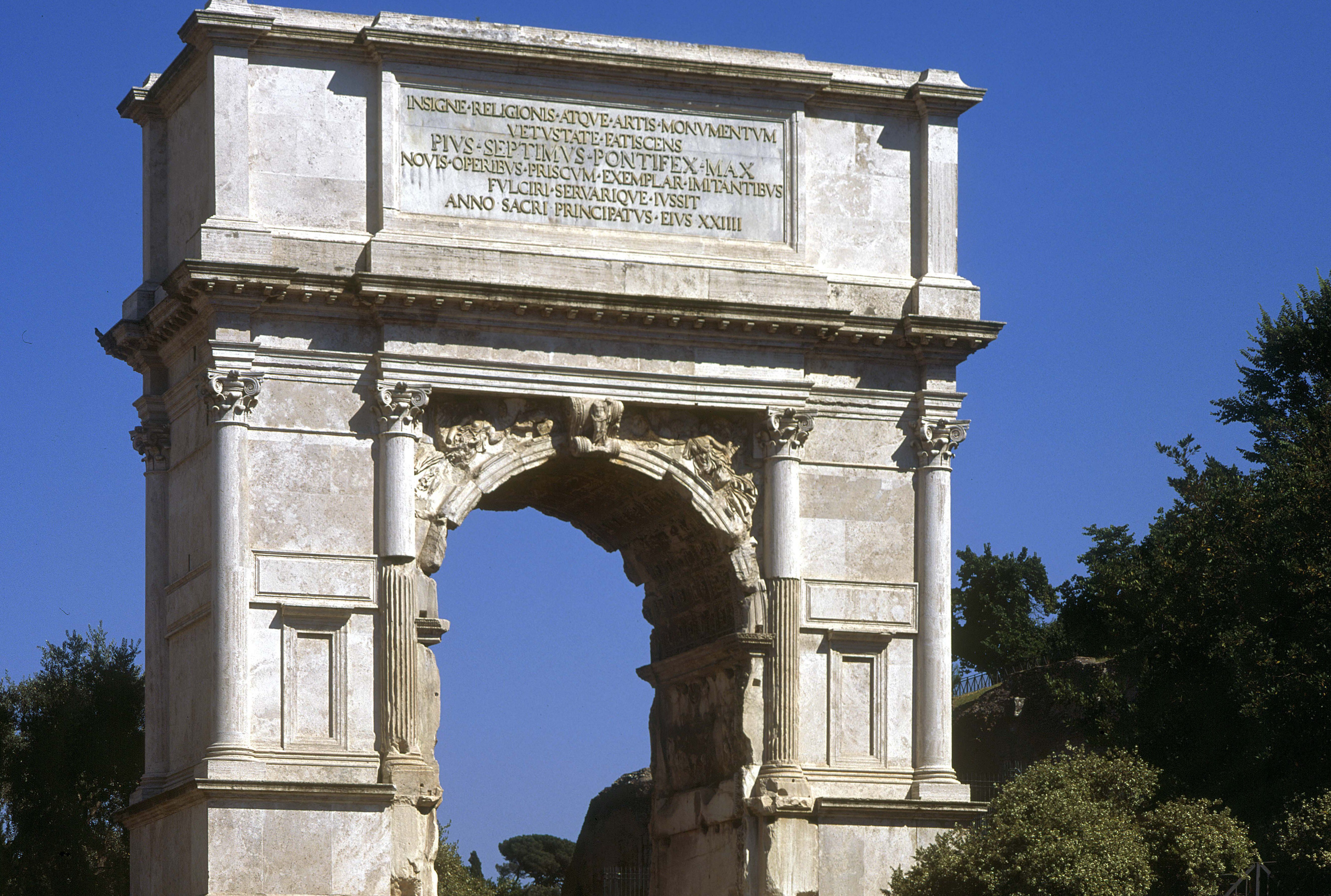 ancient Roman stone arch with engaged columns and inscription at the top