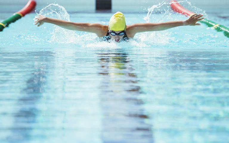 Swimmer racing butterfly stroke in pool