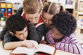 Four Girls and Boys Looking at the Same Textbook in a Classroom at Primary School