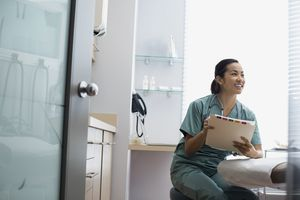 Smiling nurse holding medical record in examination room