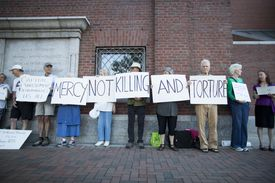 protesters hold signs for anti-death penalty