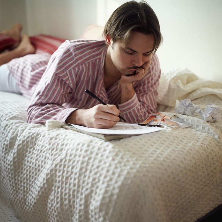 Young Man Lying on Bed Writing Letter