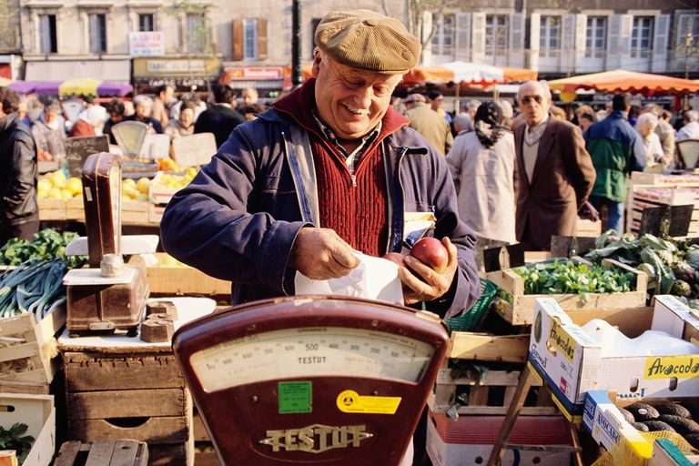A vendor at a French market weighs some produce