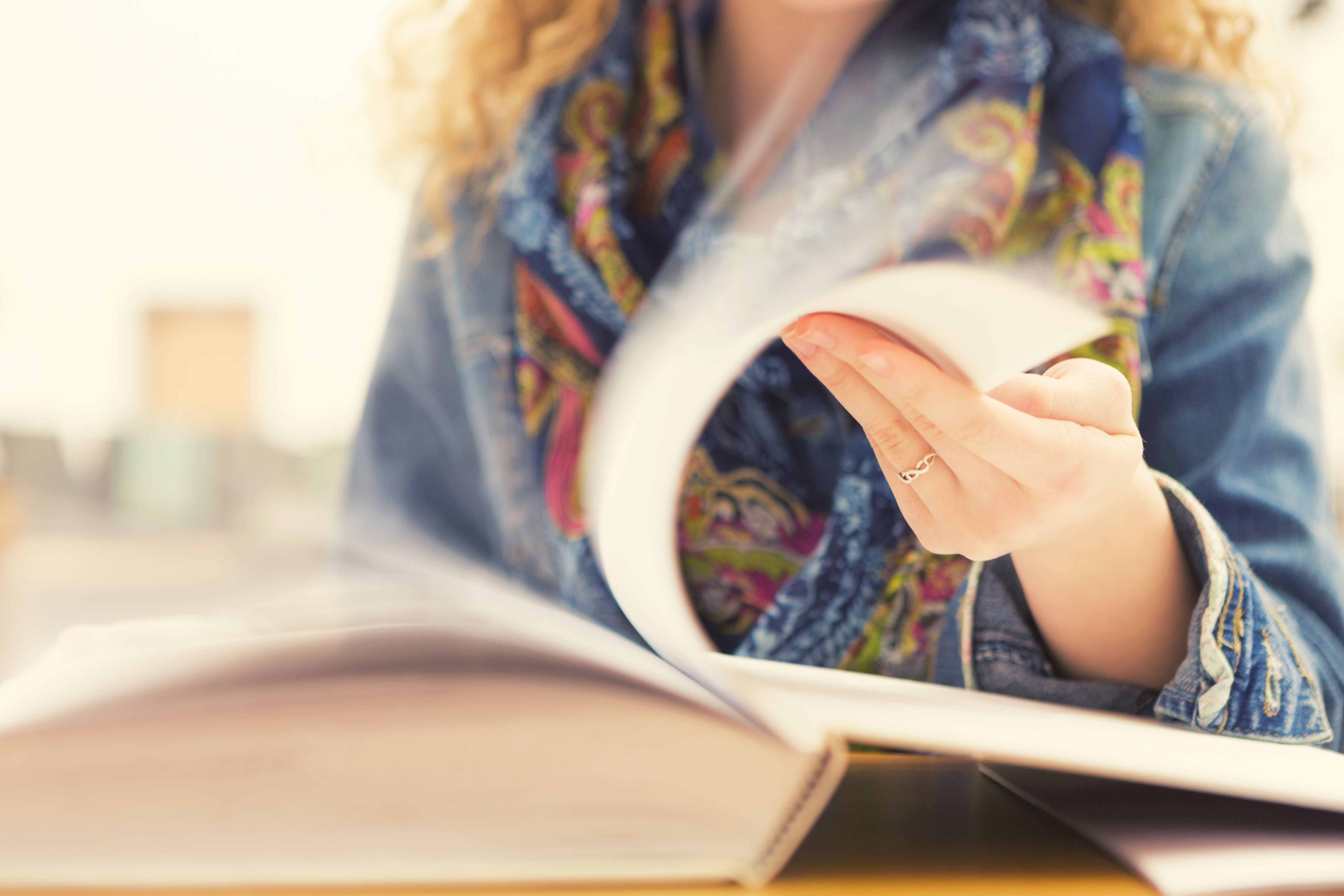 Student flipping through book; motion of turning pages