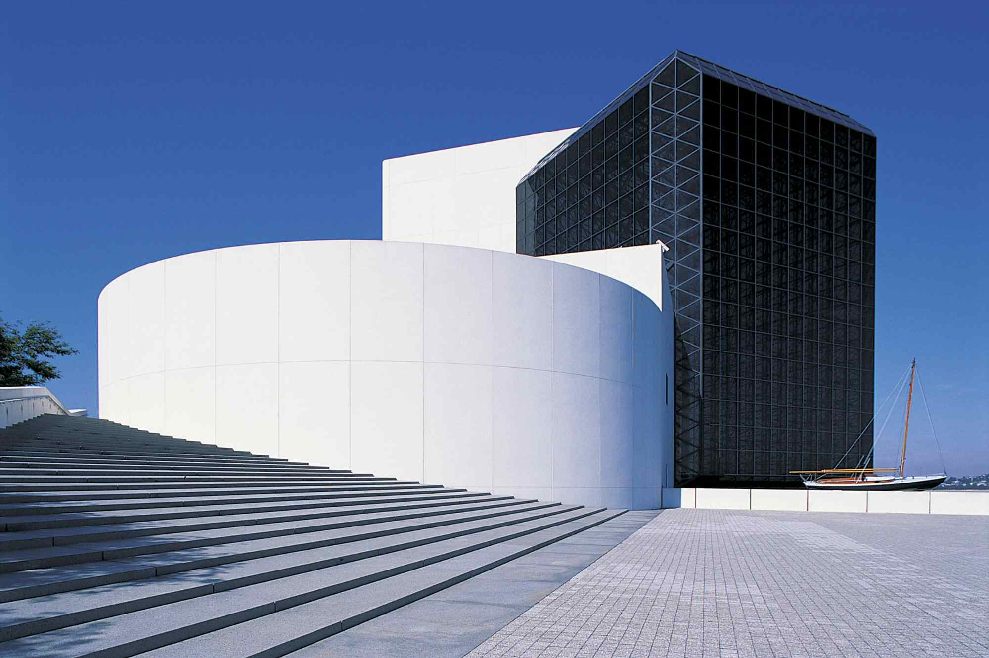 modern building, white circular near steps and glass tower in rear, sailboat on plaza