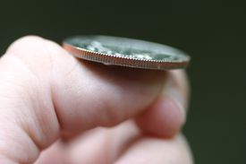 A man getting ready to flip a coin