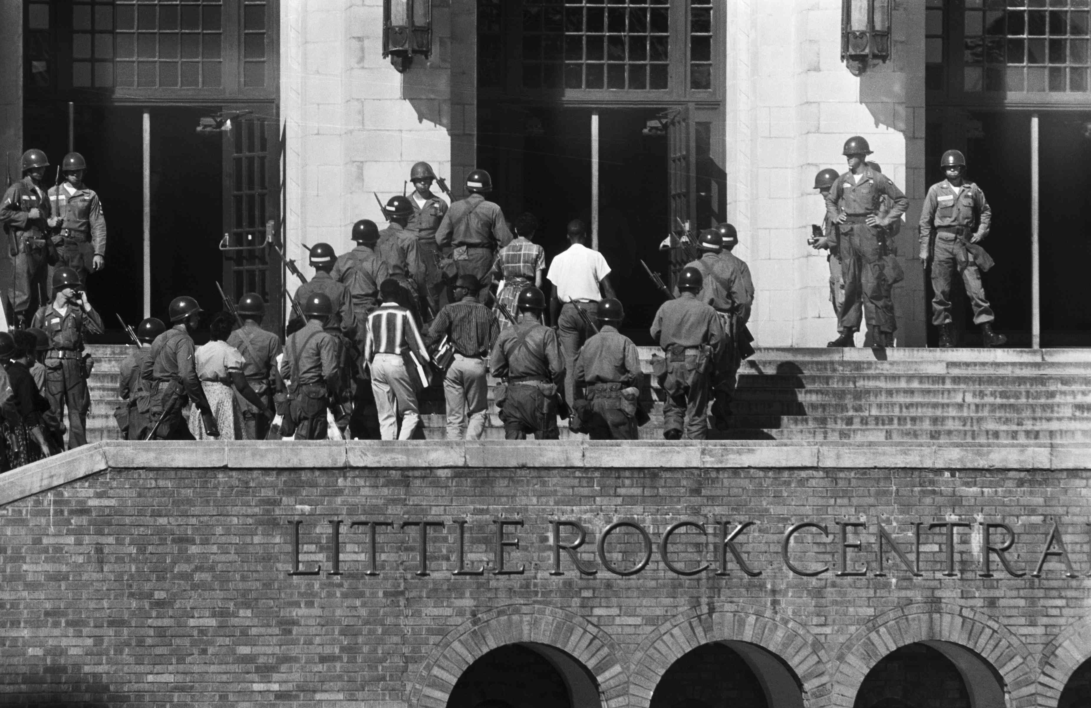 African American students being protected by U.S. soldiers as they enter Little Rock Central High School
