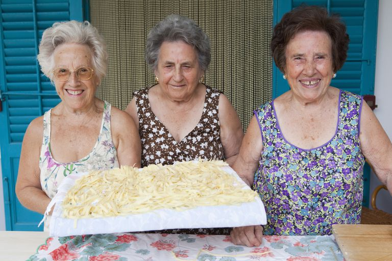 Older woman with a tray of pastaa