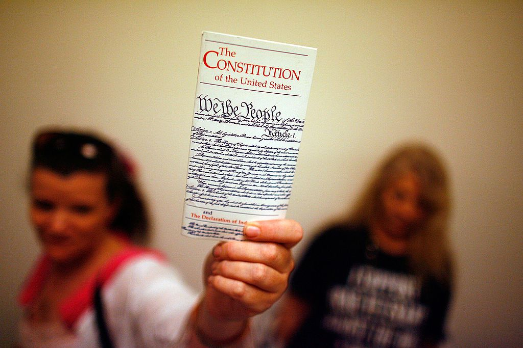 Elementary school teacher holds up a copy of the U.S. Constitution.