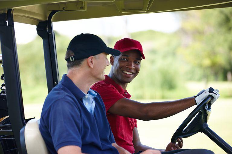 Two golfers talking in a cart