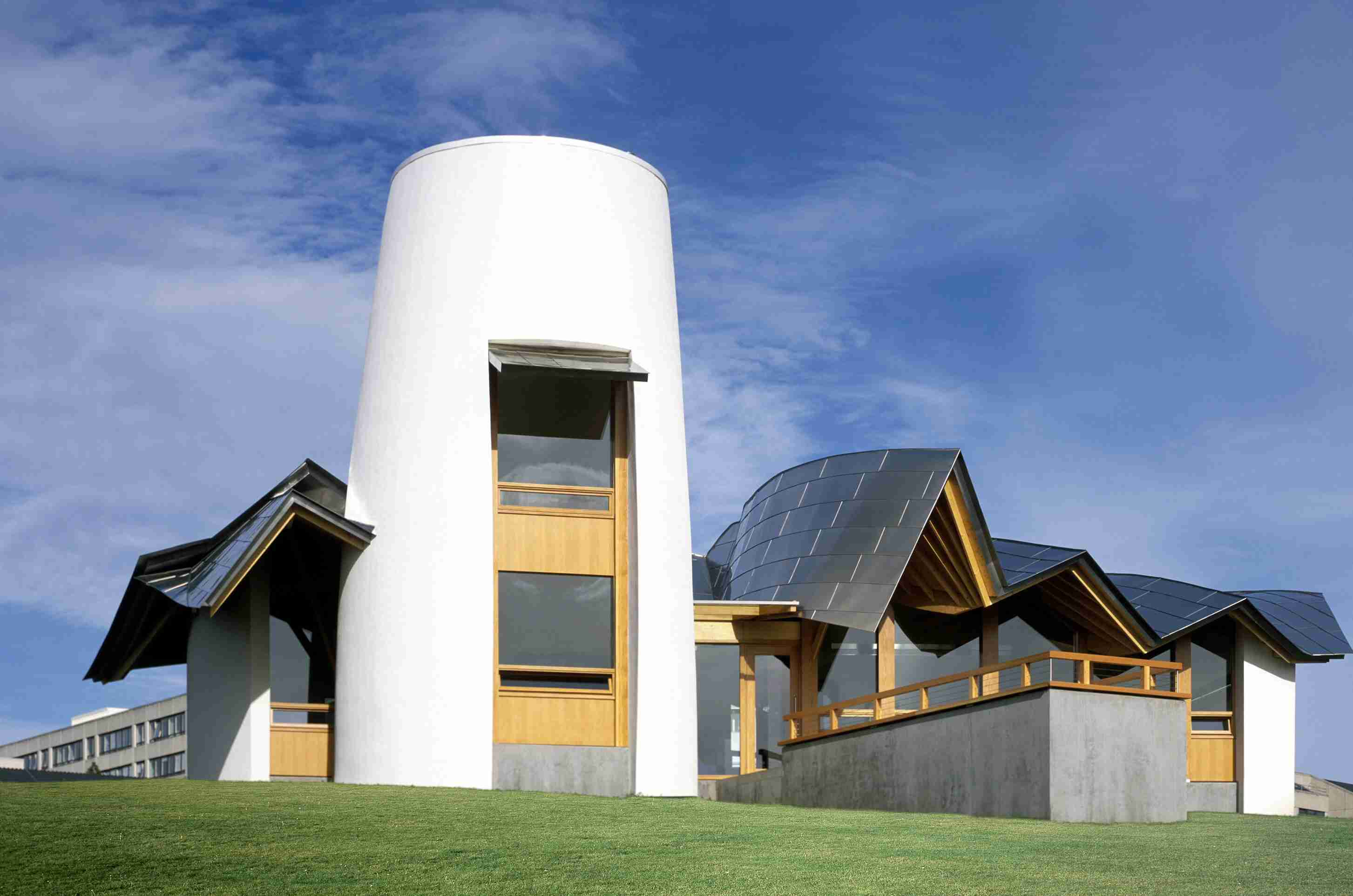 White, cottage-like building, wavy silver roof, Frank Gehry, white silo-like tower