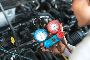 Technician checking car air conditioner refrigerant levels