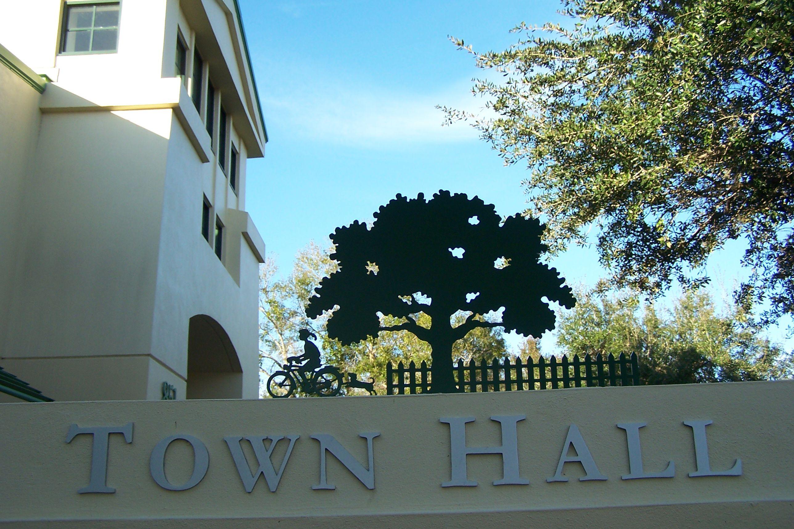 Cartel del Ayuntamiento con escultura en la parte superior: valla, árbol, niño en bicicleta perseguido por un perro