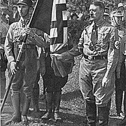 Hitler poses holding a flag