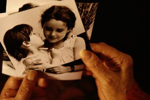 An adult looks at a vintage black-and-white photo of two children