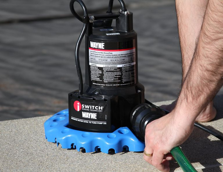 Man turning pool cover pump