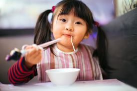 Toddler girl having noodles in restaurant