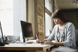 Female entrepreneur writing at desk in creative office space
