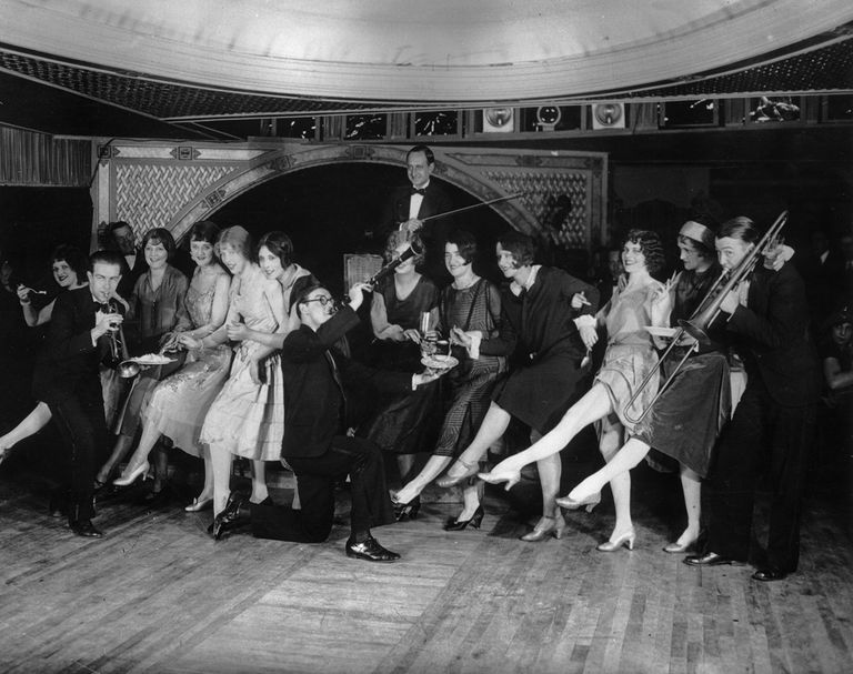 22nd January 1926: Female flappers kicking, dancing, and having fun while musicians perform during a Charleston dance contest at the Parody Club. Photo by Hulton Archive/Getty Images