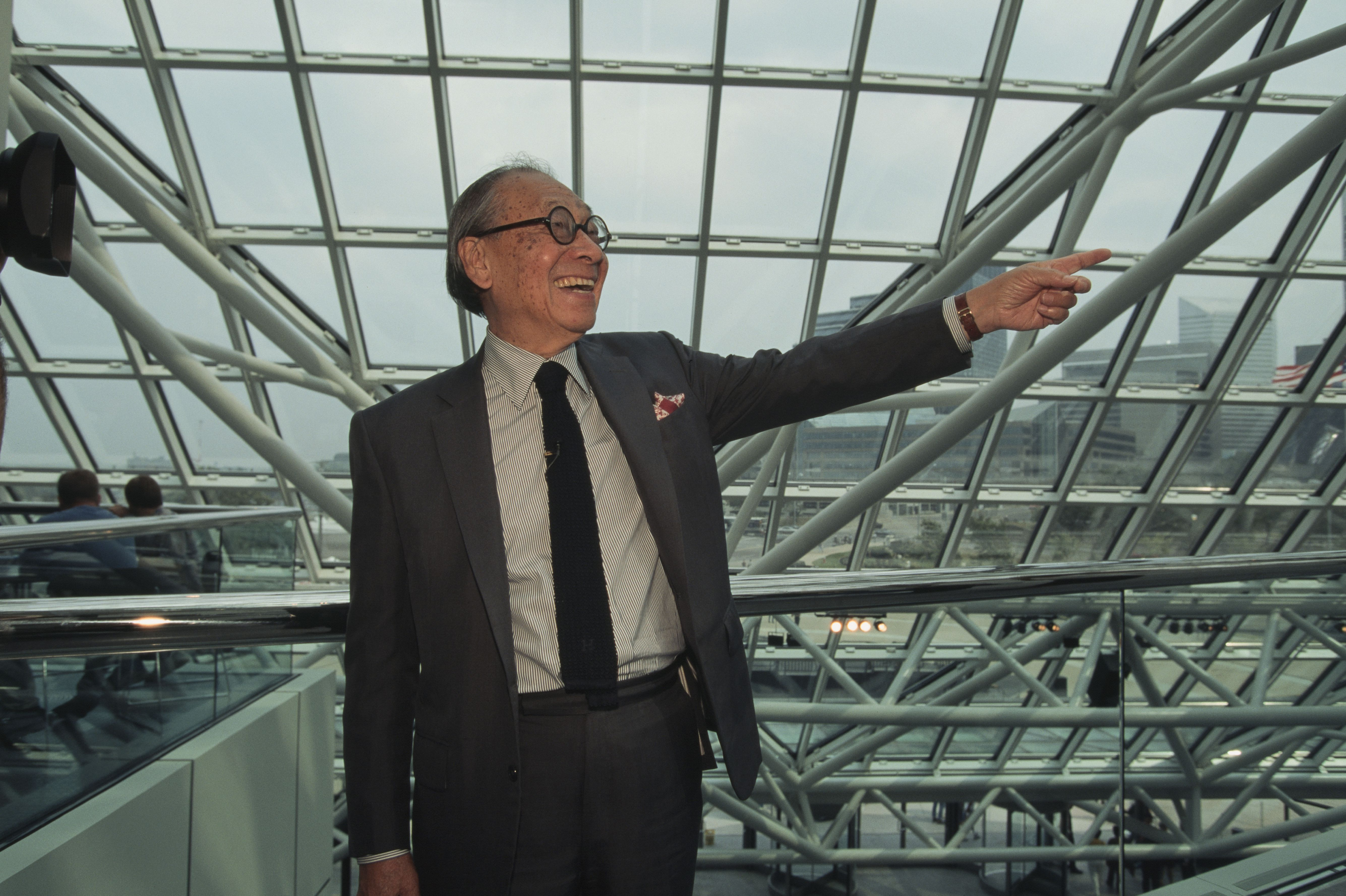 Chinese man in glasses, wearing a suit, laughing and gesturing inside a glass and steel structure