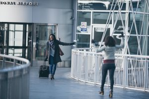 Millennial-age traveler at airport excitedly greets her friend