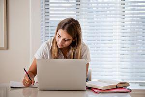 Teen girl doing homework in kitchen