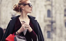 Beautiful woman wearing sunglasses in Italy with shopping bags.