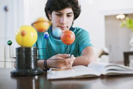 A high school student observes a model of the solar system while studying over a textbook